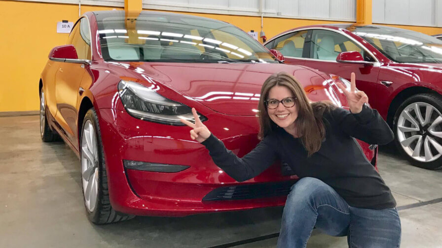 Nathalie freut sich vor ihrem neuen roten Tesla Model 3 Fahrschulauto