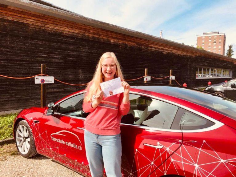 Fahrschülerin Annika steht vor dem Tesla mit bestandenem Führerausweis
