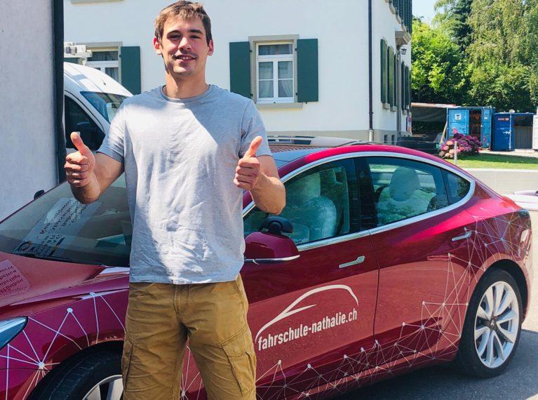 Fahrschüler Marlon steht vor dem Tesla mit bestandenem Führerausweis