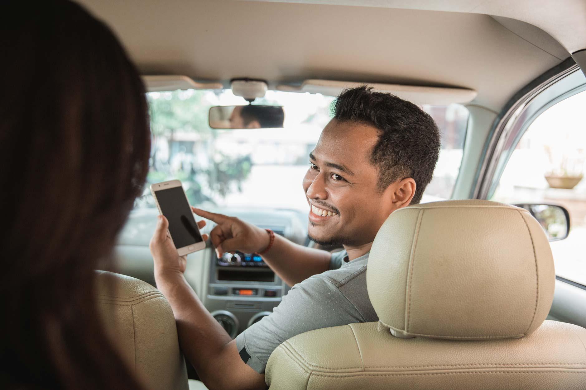 Ein glücklicher Uber-Fahrer frägt den Kunden wohin er möchte