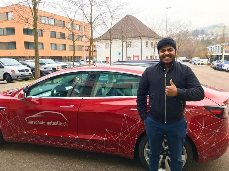Uber-Fahrschüler Kerupeensteht vor dem Tesla und hat die Taxi Prüfung bestanden