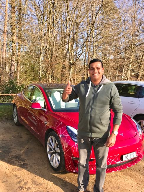 Uber-Fahrschüler Subesh steht vor dem Tesla und hat die Taxi Prüfung bestanden
