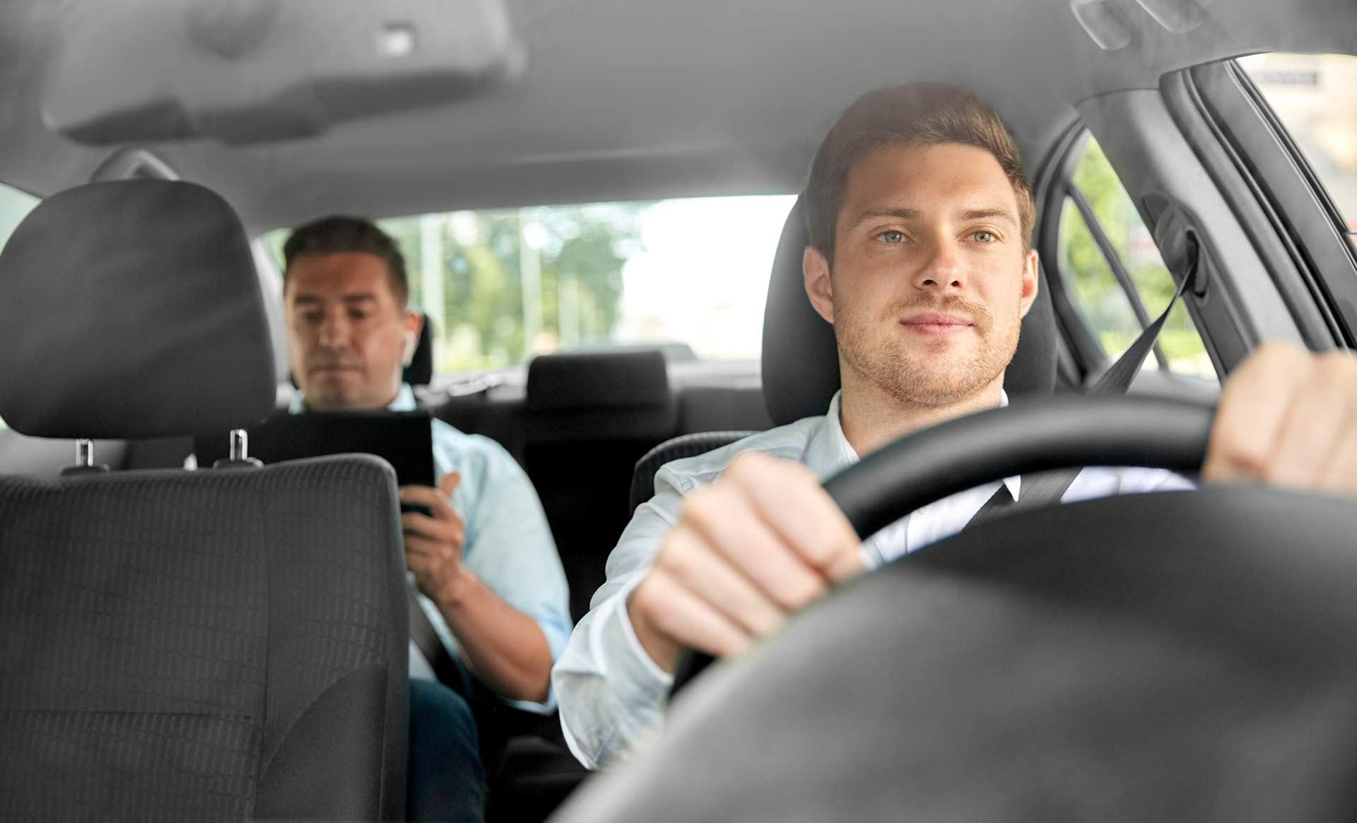 Männlicher Taxifahrer fährt den Kunden zum gewünschten Ort